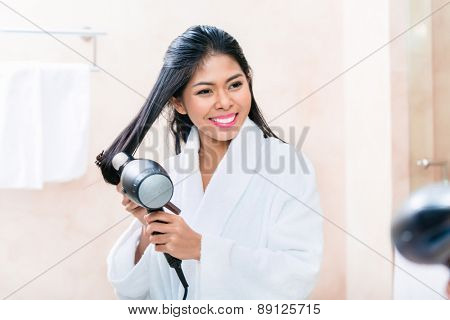 Asian woman in bathroom drying hair with blow dryer