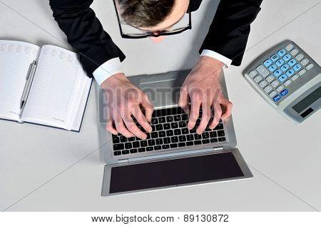 Business man writing at laptop