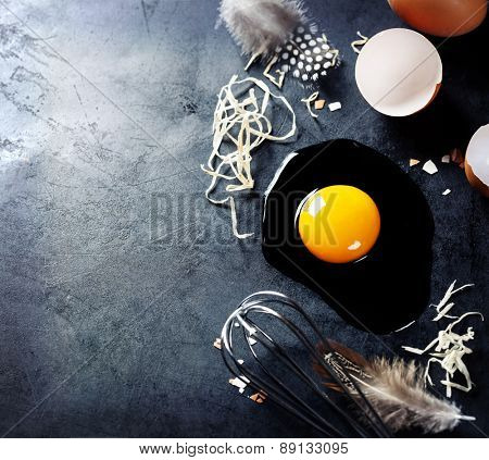 Fresh eggs with straw and  feathers  on a dark background