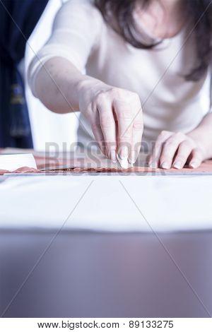Dressmaker Marking A Fabric.