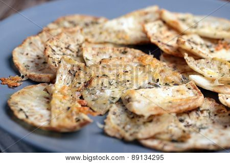 Closeup view of roasted slices of celery on a blue plate