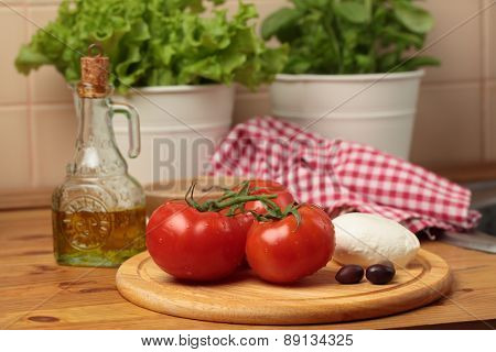 Tomatoes, mozzarella, kalamata olives and olive oil on a table in a domestic kitchen