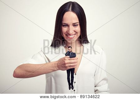 smiley woman holding small wearied man in her fist over light grey background