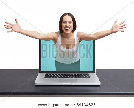 laughing woman come out from laptop and stretching out her hands against white background