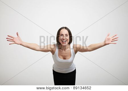 happy woman stretching out her hands to the camera over light grey background