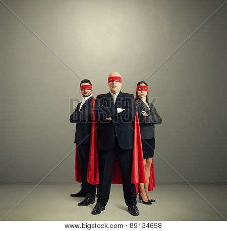 full length portrait of three superheroes in formal wear and red mask with cloak over light grey background