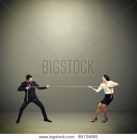 woman and man in formal wear pulling the rope over dark grey background