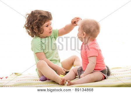 Toddler Boy Showing An Egg To A Baby Girl