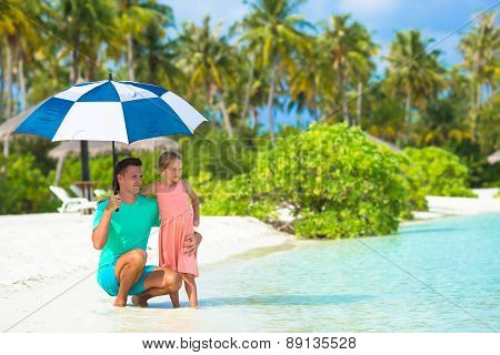 Father and little girl with umbrella hiding from sun at beach