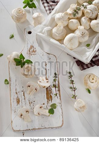Whole White Button Mushrooms  On A Wooden Board.
