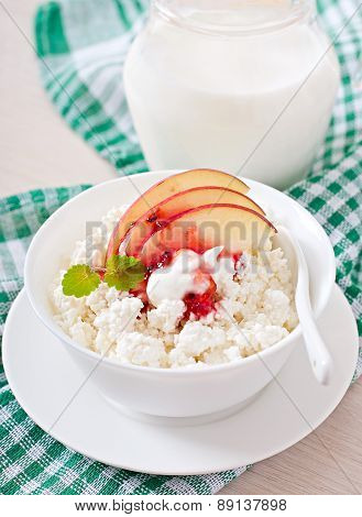 Cottage cheese with apple, berry syrup and sour cream for breakfast close up