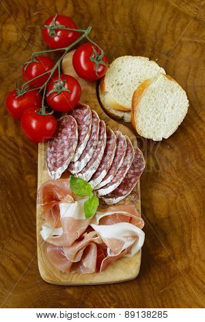 parma ham (jamon) and delicacy smoked sausage (salami) on a wooden board