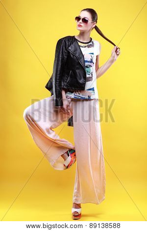 A photo of beautiful girl is in fashion style on  yellow  background, glamour