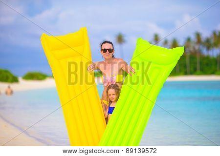 Little girl and happy mother with air mattress on summer vacation