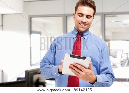 Portrait of a smiling businessman using a tablet computer in his office