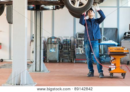 Mechanici changing car wheel in auto repair shop