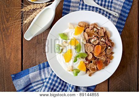 Healthy dessert with muesli and fruit in a white plate on the table