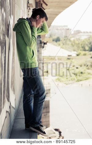 Sad young man in depression standing on the bridge