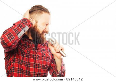 Life style concept: a young man with a beard wearing a white shirt holding a microphone and singing. Hipster style. Over white background.