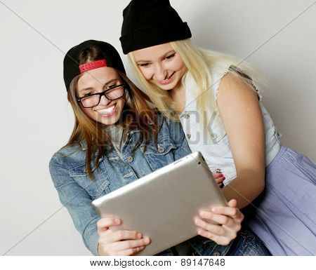 Two pretty hipster girls taking a self portrait with a tablet, over white background, not isolated