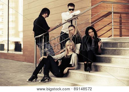 Young fashion men and women sitting on the steps