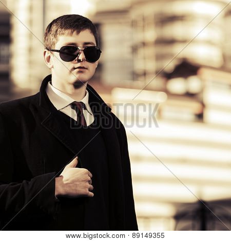 Young fashion business man walking on a city street