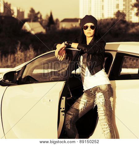 Young fashion punk woman by her car