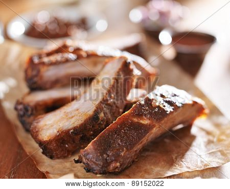 grilled pork spare ribs in barbecue sauce on wooden cutting board