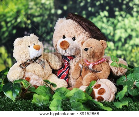A toy father, son and daughter bear cuddled together on the grass near the woods.