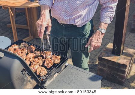 Senior Man Grilling Meat On Barbecue