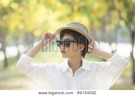 Portrait Of Young Beautiful Asian Woman Wearing Sun Glasses And Straw Hat Against Yellow Flowers Blo