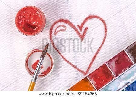 artist's brush on a background painted red heart. Top view.