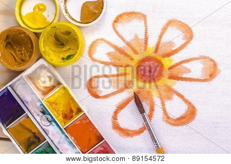 artist's brush on a background painted orange flower. View from above.