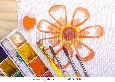artist's brush on a background painted orange flower.