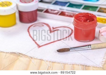artist's brush on a background painted red heart