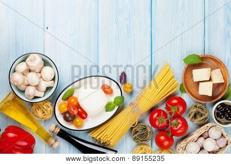 Mozzarella, tomatoes, basil and olive oil on wooden table. Top view with copy space
