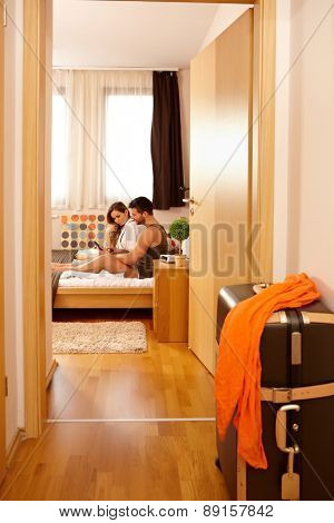 Young couple in bed on holiday, using tablet.
