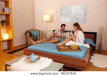 Young couple having breakfast in bed in the morning.
