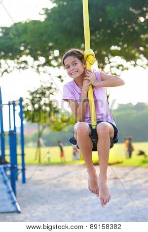 Young girl enjoying on balancing activity at the outdoor park in evening sun.
