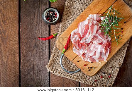 Slices of bacon on the wooden background