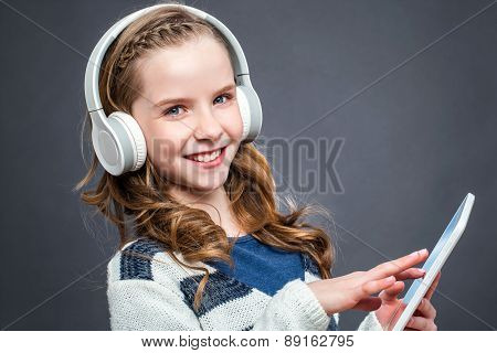 Cute Girl With Head Phones And Tablet.