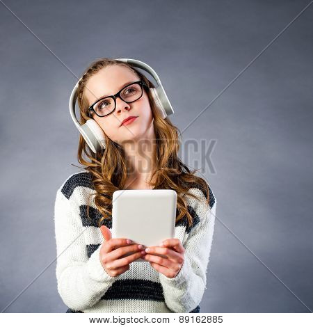 Cute Girl With Head Phones Holding Tablet.