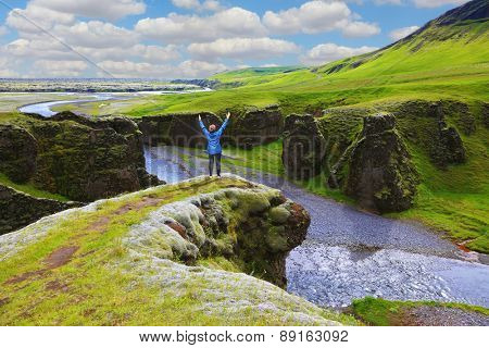 Fantastic country Iceland. Enthusiastic woman - tourist on a rock canyon  Fjadrargljufur