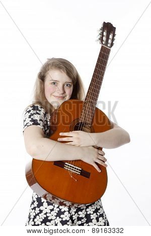 Smiling Teenage Girl In Dress Holds Guitar In Studio