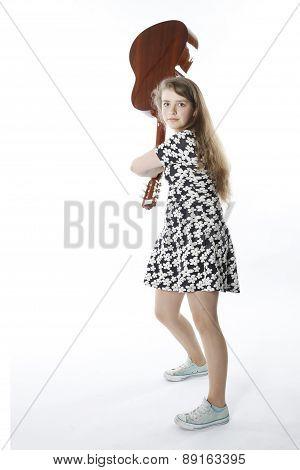 Smiling Teenage Girl In Dress Swings Guitar In Studio