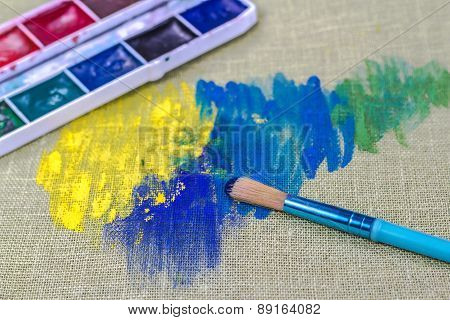 Brush with colorful paint on green canvas