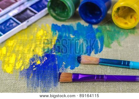 canvas, brush and bank with green paint