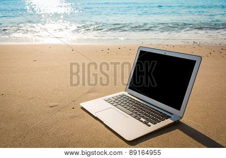 Laptop on the beach in summer time