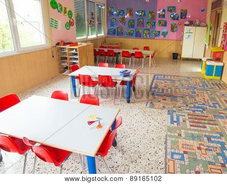 Classromm Of Kindergarten With Tables And Small Red Chairs