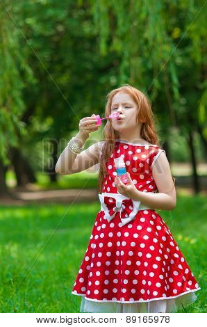 Beautiful dress girl with soap bubbles